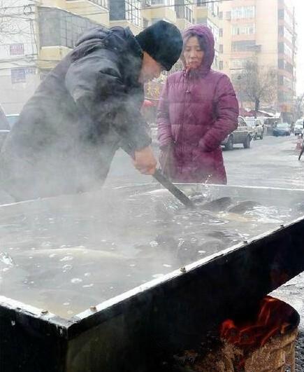 """一张图告诉你哈尔滨有多冷!数九寒天,卖鱼人支起大锅将""""活鱼加热卖""""。"""
