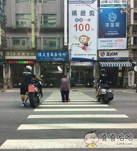 老婆婆过马路比较慢,红灯亮的时候还只走了一半,一对骑摩托车的情侣过去护航,保护婆婆过马路