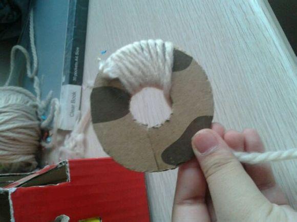 把两张圆重合在一起,把毛线缠绕上,像这样